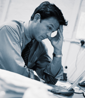 Supply Chain Scene, image of a stressed out person looking at a laptop
