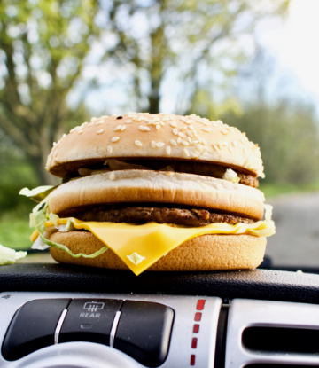 Supply Chain Scene, image of a cheeseburger on a car dashboard