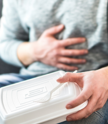 SCS, image of man holding a takeout container whle clutching his stomach