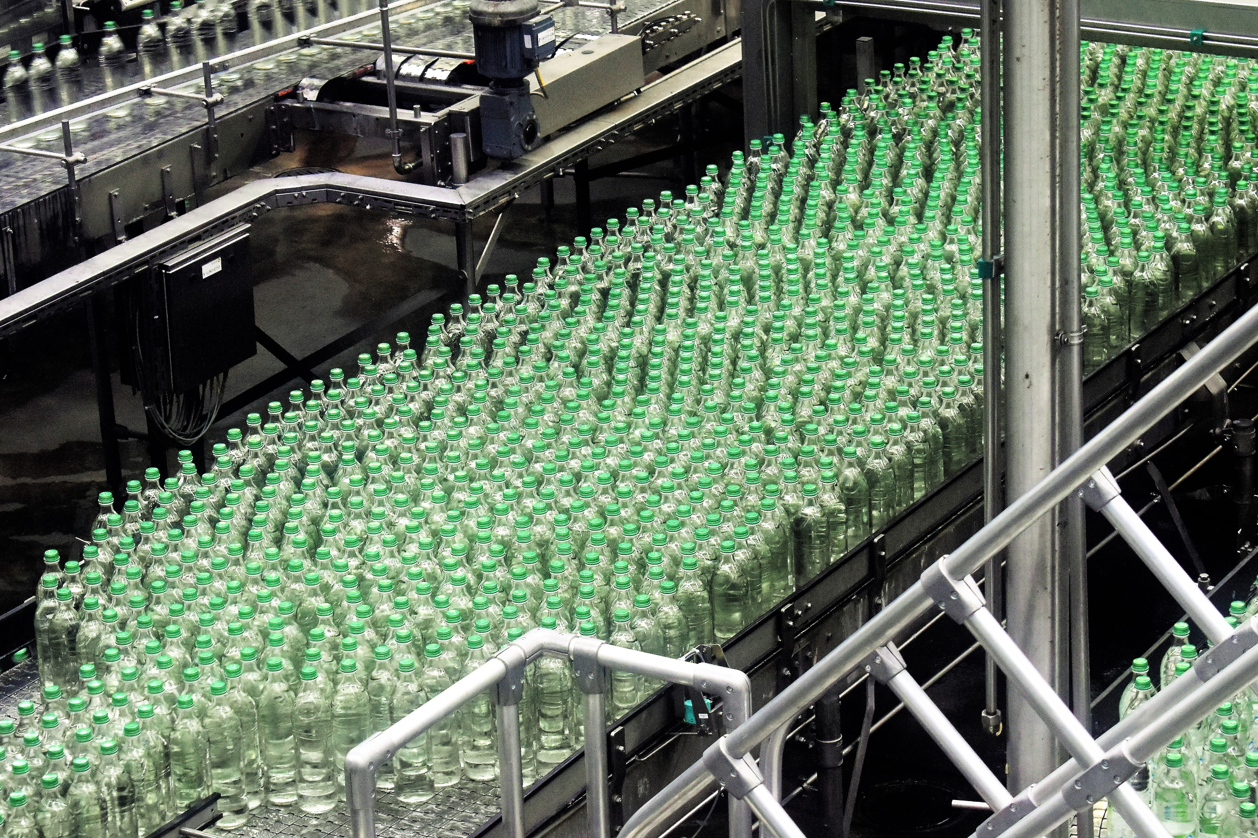 Green glass bottles on a manufacturing line.