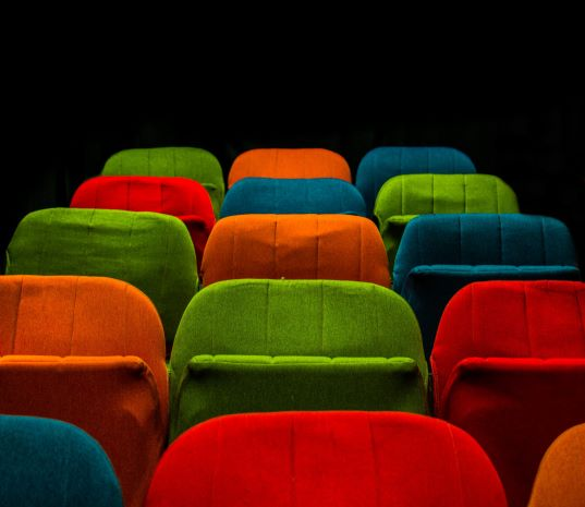 Multi-colored plush auditorium chairs.