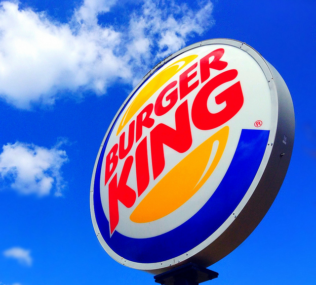 Burger King sign set against blue sky with white clouds.