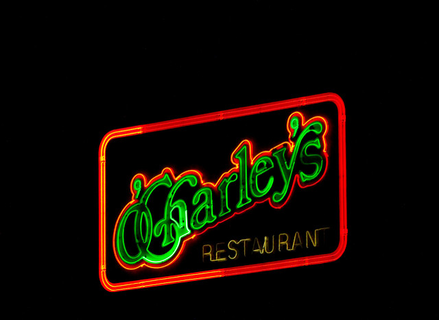 Neon green and red O'Charley's sign at night.