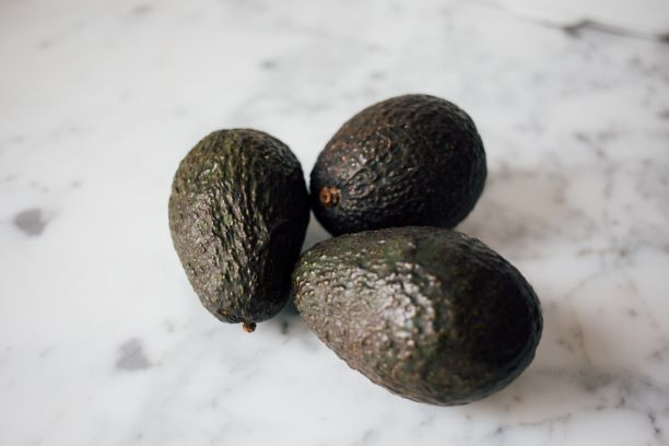 3 ripe avocados on top of marble counter