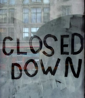 "The words ""closed down"" written on a dirty window with a reflection of a building across the street."