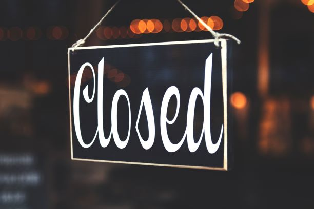 """Closed"" sign on glass door."