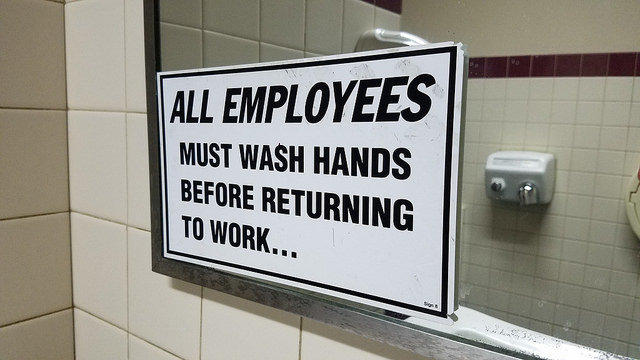 """All Employees Must Wash Hands Before Returning to Work"" sign on mirror with reflection of hand dryer in background"