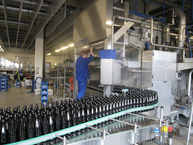 Man in blue uniform working at bottling plant.