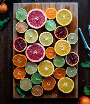 Colorful citrus slices on wooden cutting board