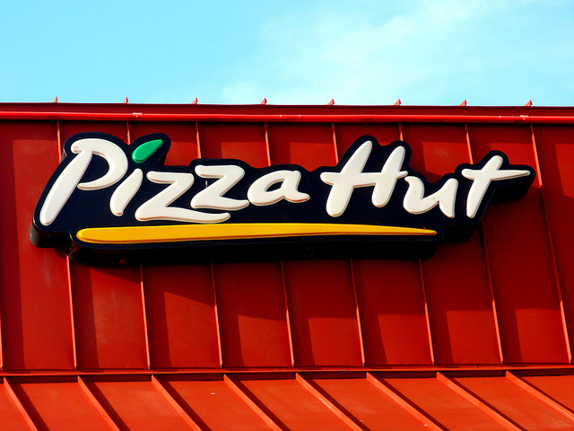 Pizza Hut sign across red, metal roof