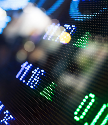 Supply Chain Scene, image of a stock ticker board out of focus