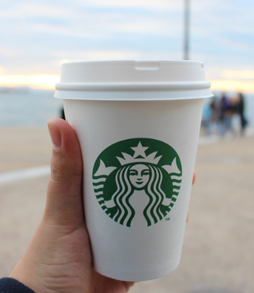 Supply Chain Scene, image of a hand holding a starbucks cup at the beach