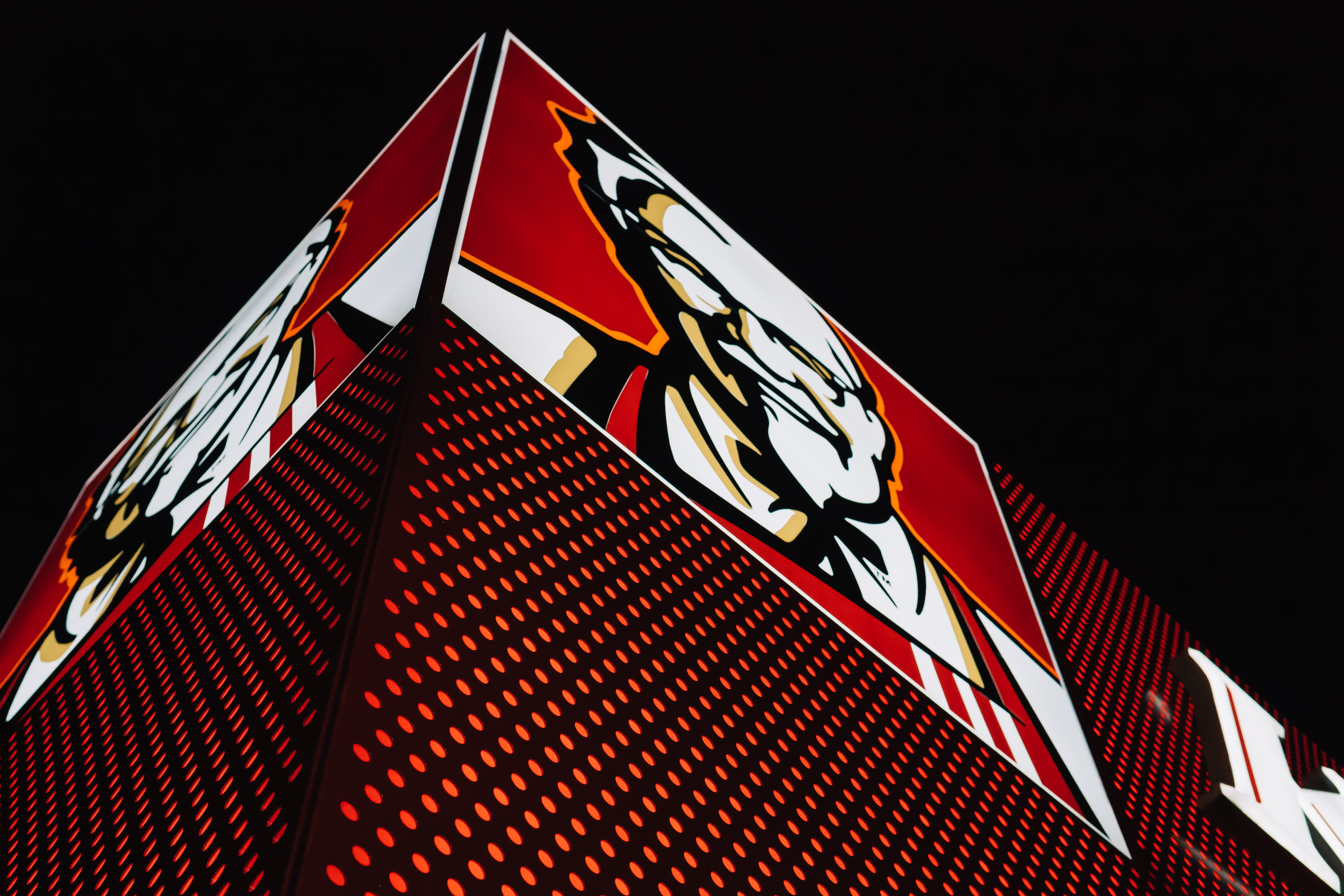 Supply Chain Scene, image of a lighted KFC sign on a corner building