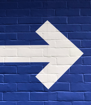 Supply Chain Scene, image of a white arrow painted on a blue wall
