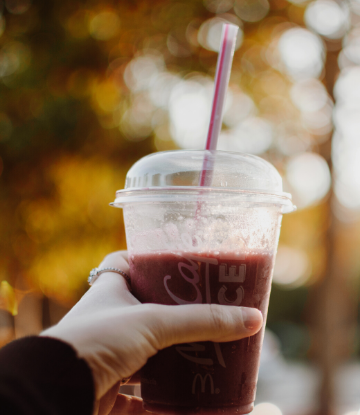 SCS, image of a hand holding a plastic coffee drink cup with straw